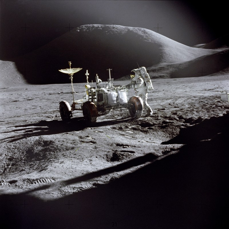 "Lunar module pilot James Irwin works at the Lunar Roving Vehicle during the first Apollo 15 lunar surface extravehicular activity at the Hadley-Apennine landing site. The shadow of the Lunar Module ""Falcon"" is in the foreground. This view is looking northeast, with Mount Hadley in the background. This photograph was taken by mission commander David Scott. (Photo: NASA)"