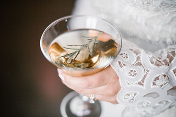 Bride holding a rosemary martini
