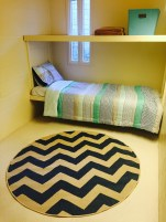 Unlocked FIRS dorm rooms are outfitted with patterned quilts, pillows and rugs.