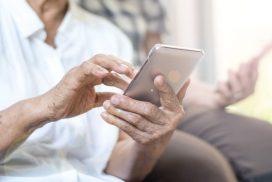 Altere Menschen Hände bedienen ein Smartphone