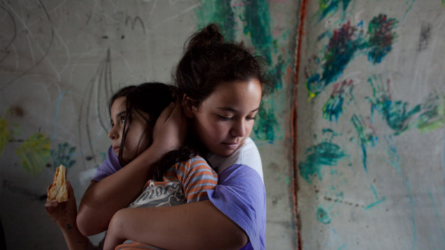 An Israeli girl holds her sister as they take cover in a large concrete pipe used as a bomb shelter during a rocket attack from the Gaza Strip on Monday in Nitzan, Israel. (Photo: CNN)