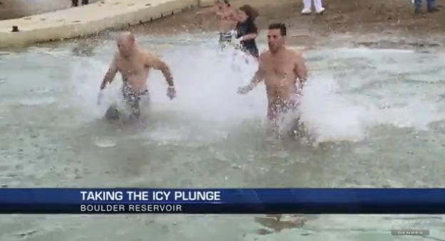 Two men run into Boulder Reservoir for the Polar Plunge in 2014.