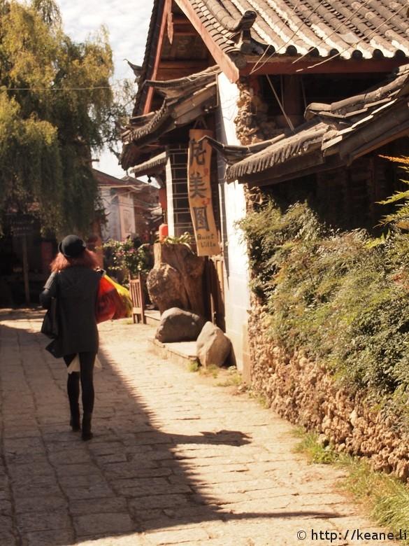 Woman walks with shopping bags in Shu He Ancient City in Lijiang