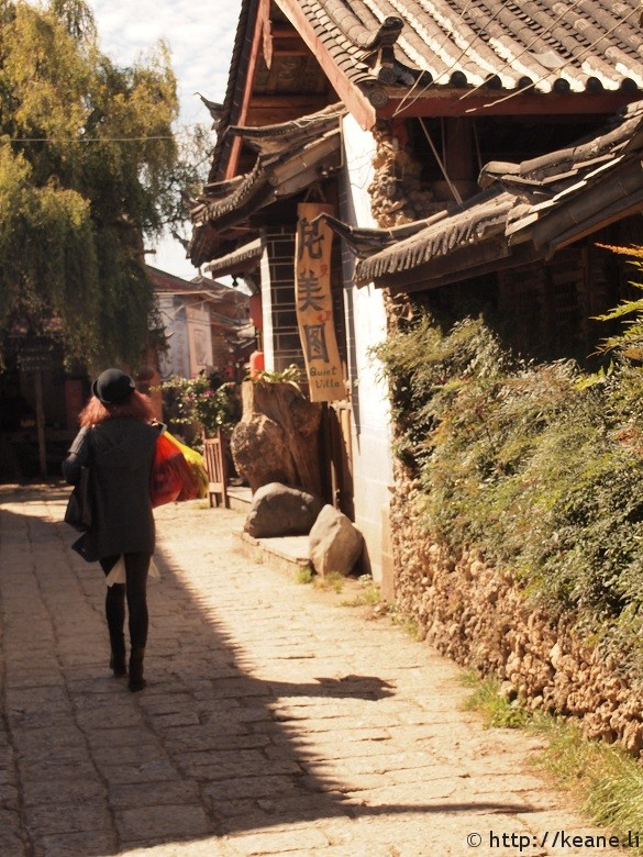Woman walks with shopping bags in Shu He Ancient City in Lijiang