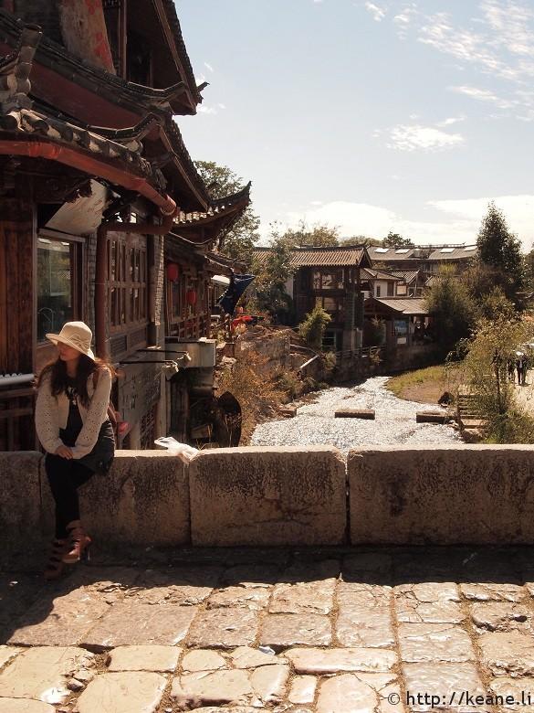 Woman sitting along Qinglong Bridge in Shu He Ancient City in Lijiang