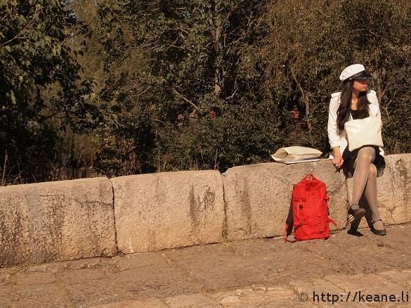 Fashionable girl sitting along Qinglong Bridge in Shu He Ancient Town