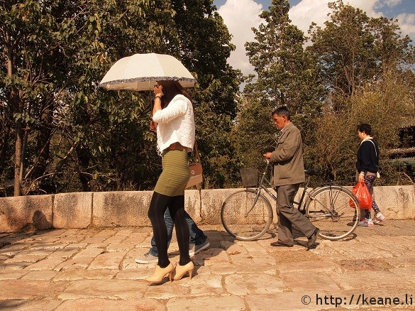 Woman with umbrella and heels on Qinglong Bridge in Shu He Ancient City