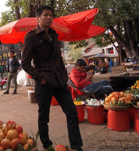 Two guys inadvertently pose by the fruit stands in Shu He Ancient City