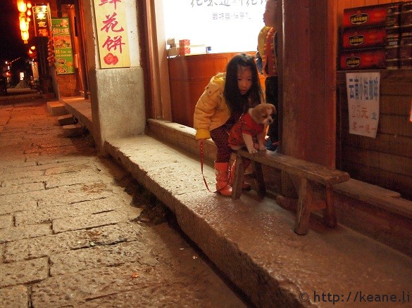 Little girl plays with dog in Lijiang's Shu He Ancient City at night