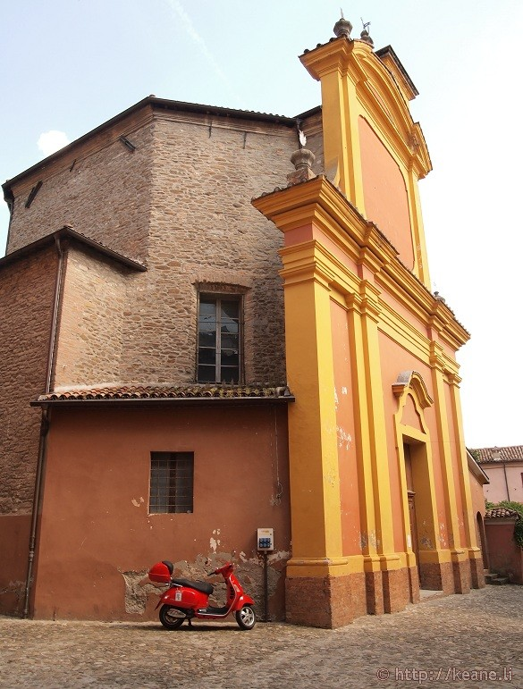 Bright yellow church and a red scooter in Brisighella