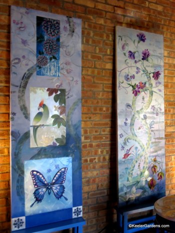 Two tall canvas paintings by Meg Fine Art, sit side by side at an art show. Heavy blue tones cover both with as the one on the left depicts a vining flower with accents of a red cardinal and the one on the right features a beautiful blue butterfly.