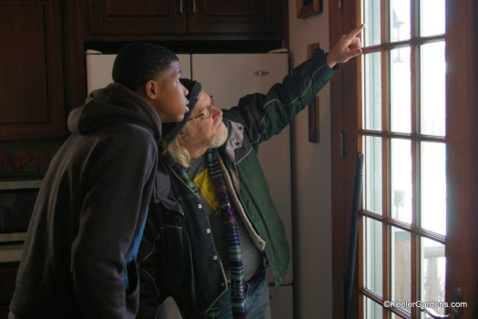 Workman and intern look out french doors at Keeler Gardens. Workman is pointing up towards the needed repair and intern is looking and listening intently.