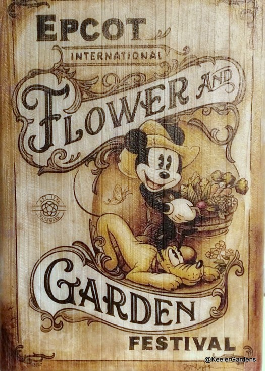 A white washed wooden sign for the Epcot International Flower and Garden Festival showing Mickey Mouse in overalls and a farm hat carrying what appears to be a buschell of corn tulips and asperagas while pluto eagerly looks on under foot.