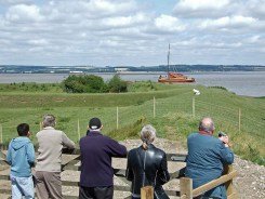 Visitors look on as Phyllis hoists her sails