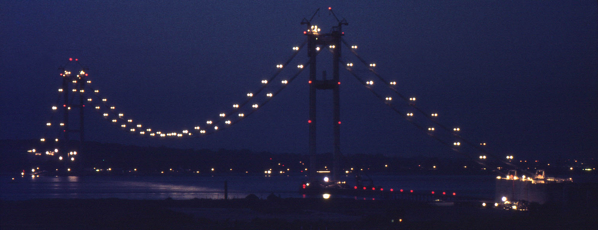 The Humber Bridge under construction - in September lit catwalks highlighted the working area for spinning the main cables