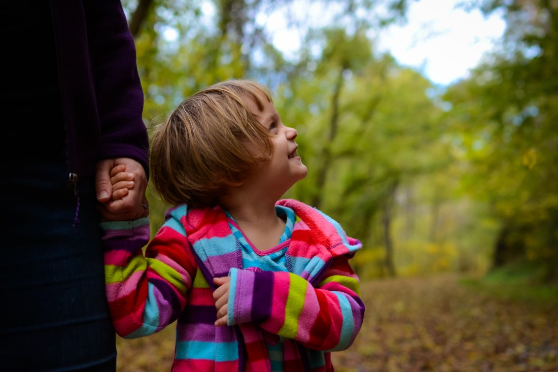 Photo of little girl holding mother's hand on wooded trail