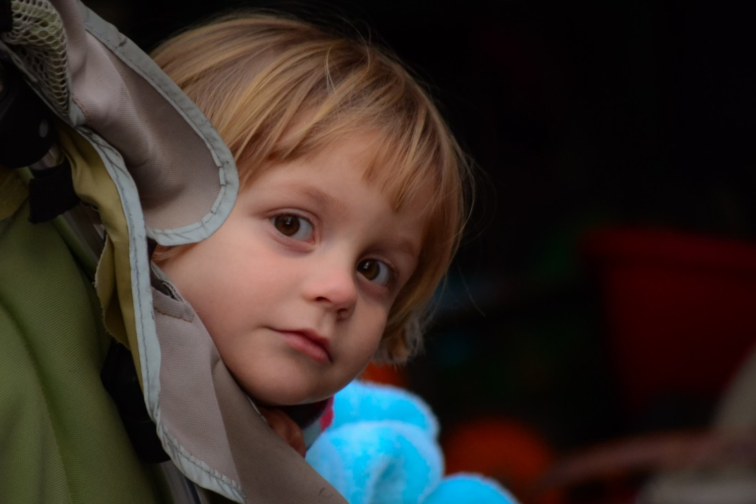 Close-up portrait of little girl peering around edge of stroller