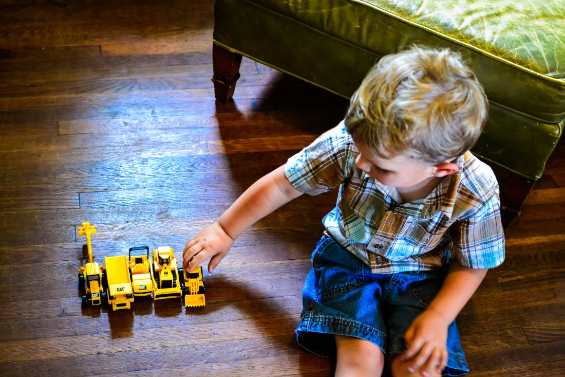 Photo of little boy in plaid shirt lining up construction vehicles on hardwood floor