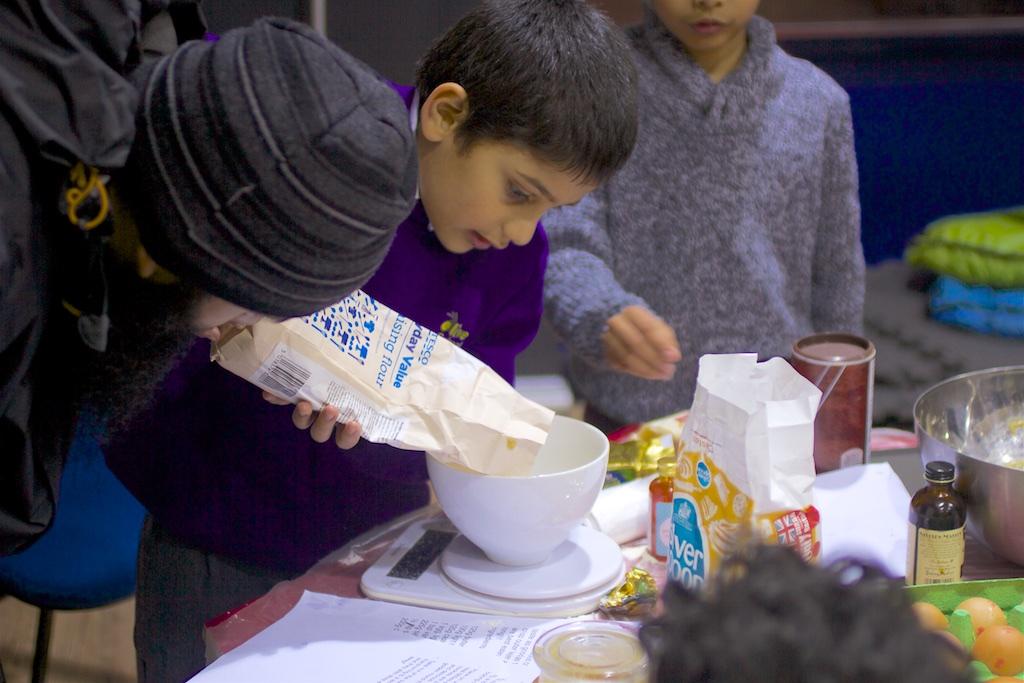 kid pouring flour into the bowl