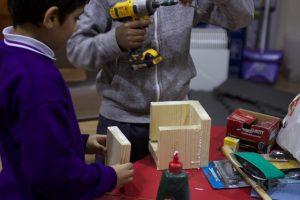 boy gluing wooden box