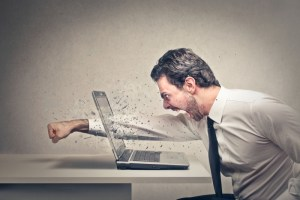 angry person punching through his laptop