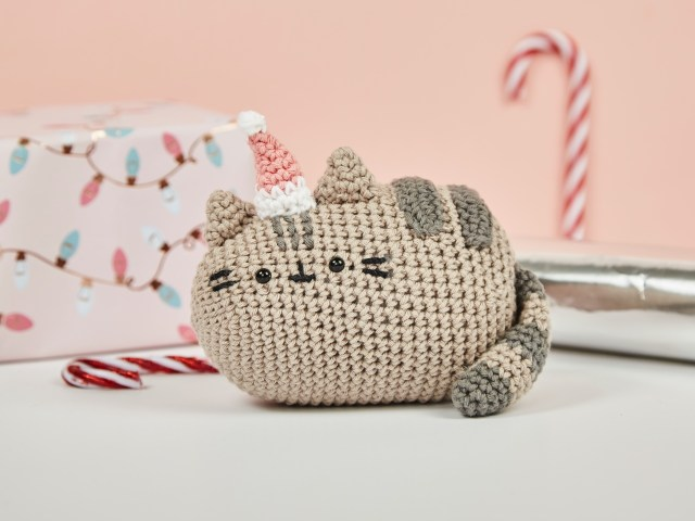Crocheted version of Pusheen the cat in a festive scene wearing a tiny Santa hat
