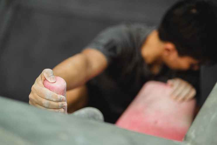 anonymous male athlete practicing rock climbing on wall in gym