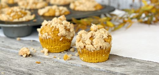 2 pumpkin muffins with muffin tin in background