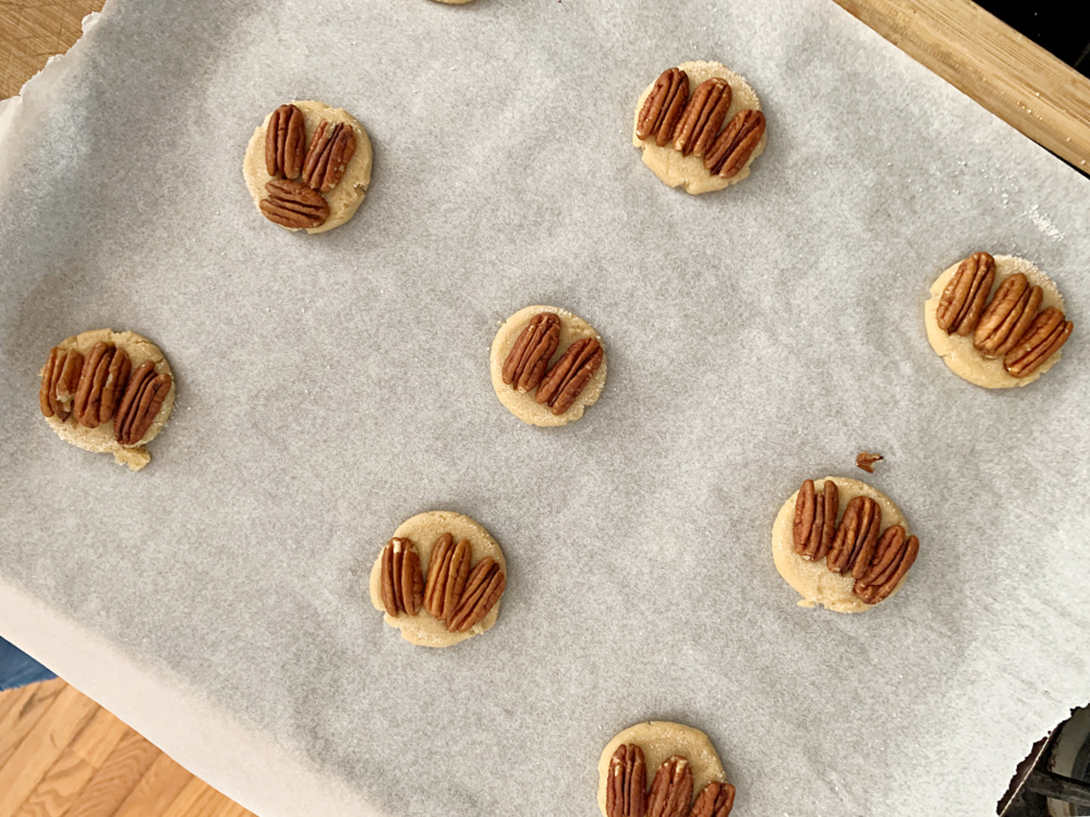 overhead view of unbaked maple cookies on cookie sheet with pecans on top