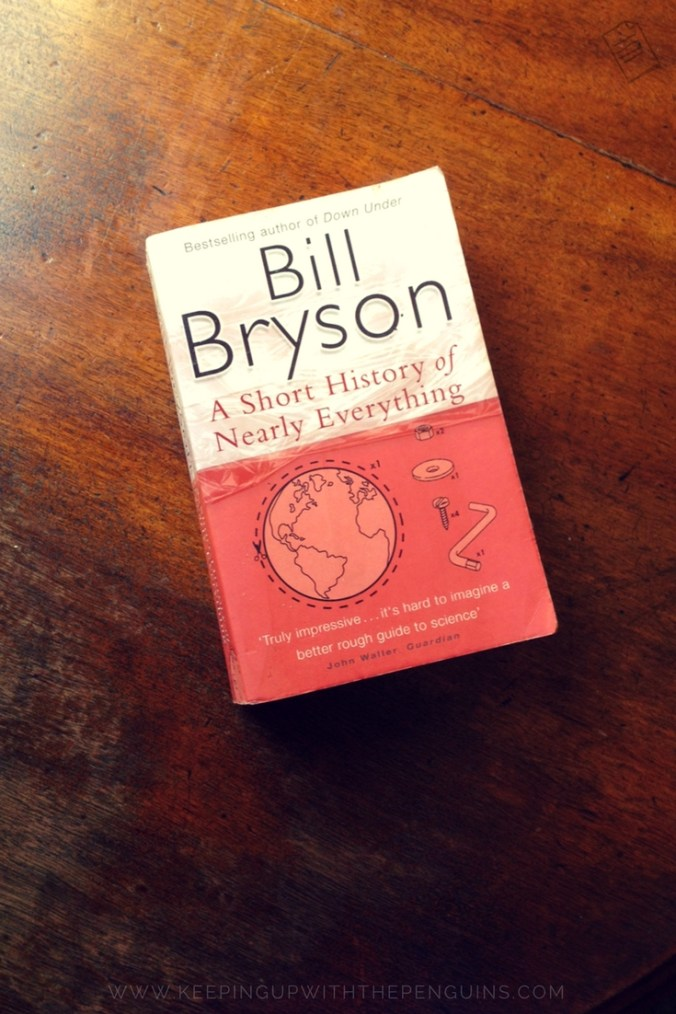 A Short History of Nearly Everything - Bill Bryson - book laid on a wooden table - Keeping Up With The Penguins
