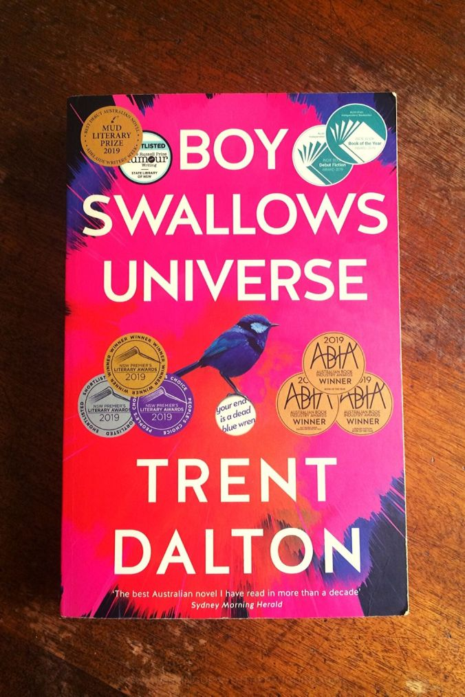 Boy Swallows Universe - Trent Dalton - Book Laid Face Up On Wooden Table - Keeping Up With The Penguins