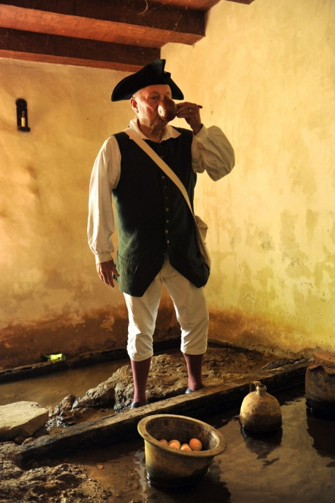 Tom Phlegar, a volunteer at the Charlotte Museum of Hitsory, shows how Colonial-era residents would get water from the springhouse. Photo: Nancy Pierce