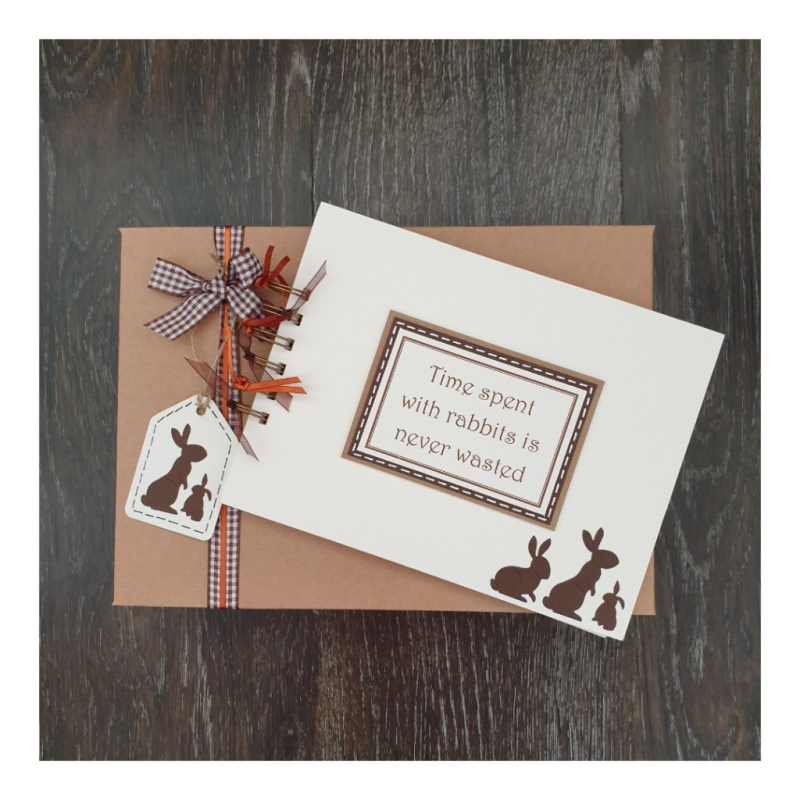 cream scrapbook with brown rabbits silhouettes sitting on a kraft brown gift box