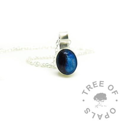Aegean blue resin sparkle mix with short dark hair, matching mystery piece necklace. Client ordered a ring and chose to have the spare cabochon set as a mystery necklace).