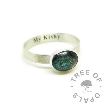 teal engraved fur ring, engraved with Times New Roman font on the inside of the band. Brushed band, mermaid teal resin sparkle mix. Image courtesy of Tree of Opals