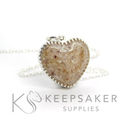umbilical cord heart necklace with a little white sparkle mix behind the cord. Scalloped setting