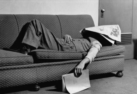 man with newspaper sleeping on the sofa