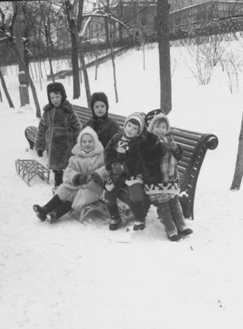Children bundled up against the cold winter weather taking a break on a bench from sleighing