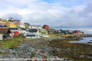 clouds over home on rocky shoreline
