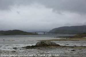 clouds over bridge and rocky beach