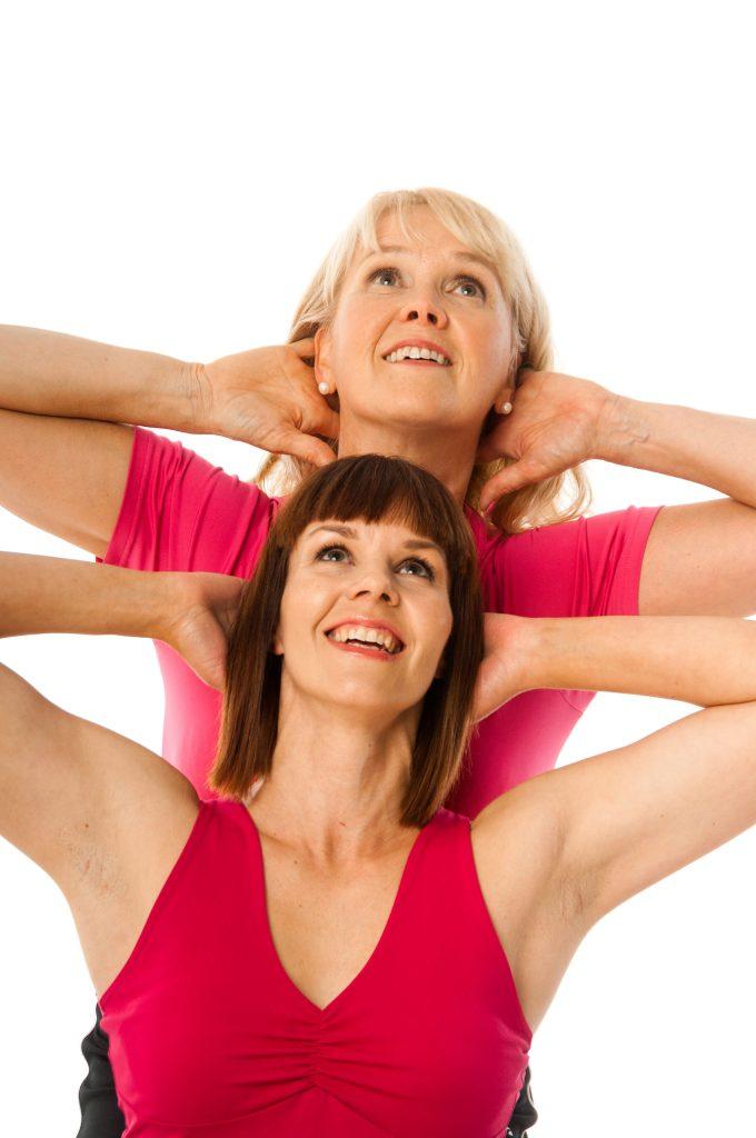 kaksi naista hymyilee ja katsoo ylöspäin kädet niskan takana