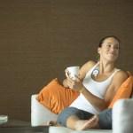 Nainen istuu sohvalla Firstbeat hyvinvointimittari rinnassa