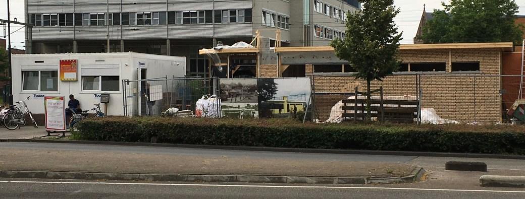 Provisorischer Verkaufscontainer und Immobilie im Wiederaufbau