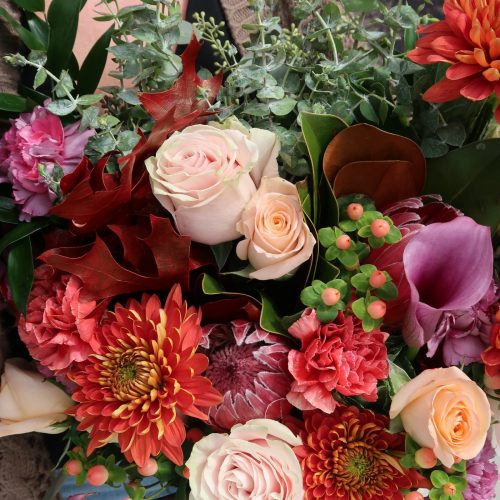 Florist holding large fall bouquet of wrapped fresh flowers, including roses, mums, calla lilies, hypericum berries and carnations