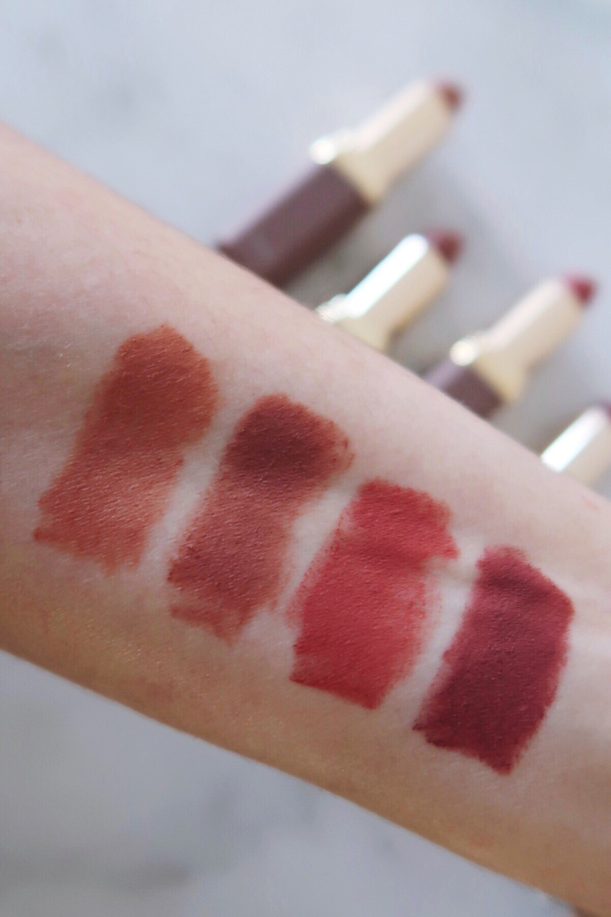 Drugstore Matte Lipstick Review - L'Oreal Colour Riche Ultra Matte Lipstick swatches on skin in natural daylight. From left to right: 983 Utmost Taupe, 978 All Out Pout, 977 Passionate Pink, 980 Rebel Rouge
