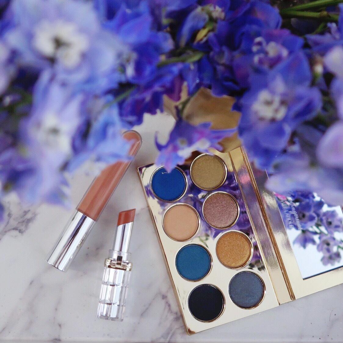 Violette Fr x Estee Lauder La Dangereuse 'Blue Dahlia' eye shadow palette on a marble tray beside of vase of fresh blue delphinium flowers, L'Oreal Colour Riche lipstick, and Becca lip gloss.