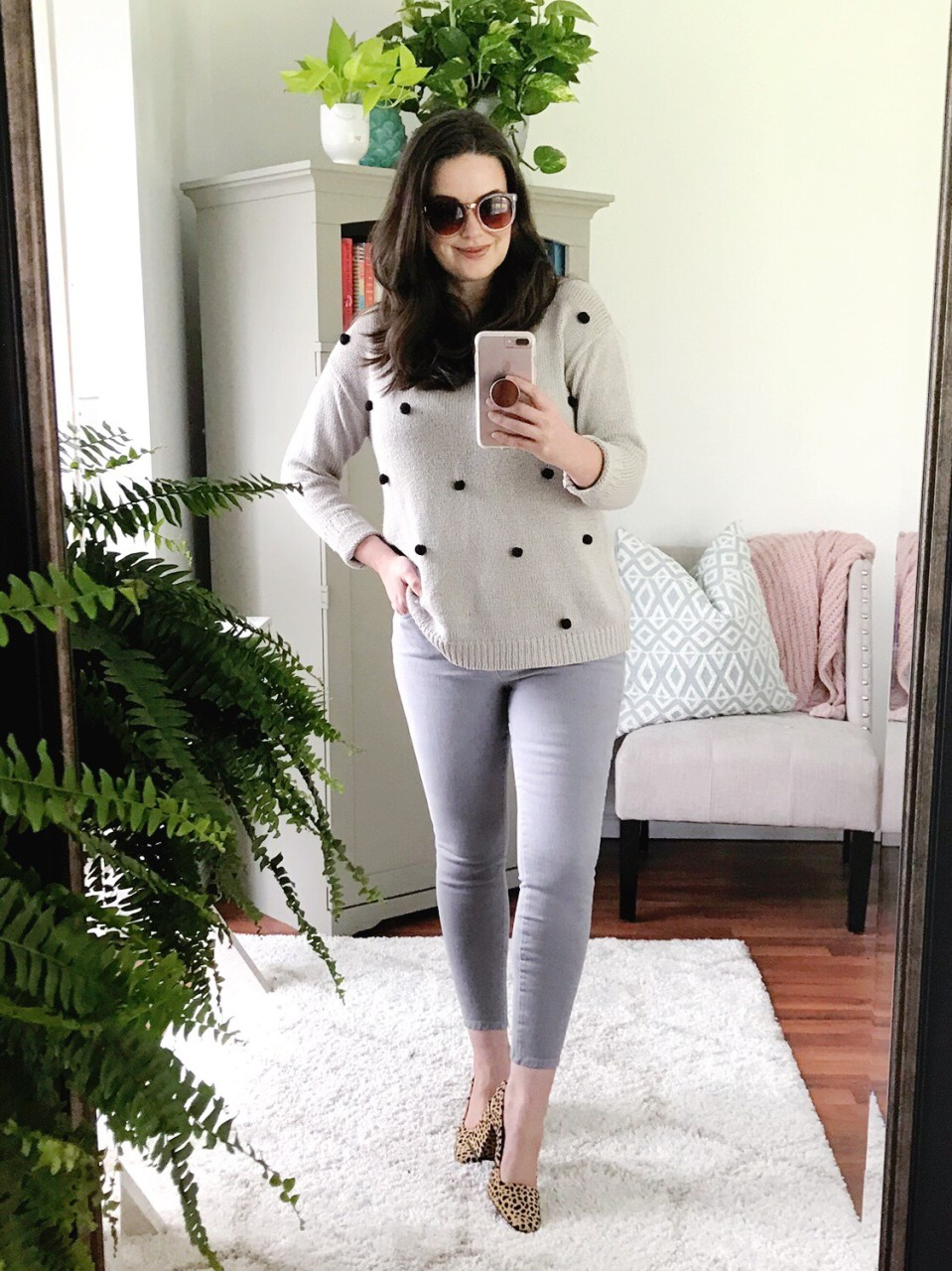 Style blogger wearing gray over-sized sweater with black pom-pom embellishments, gray skinny jeans and TOPSHOP leopard pumps.