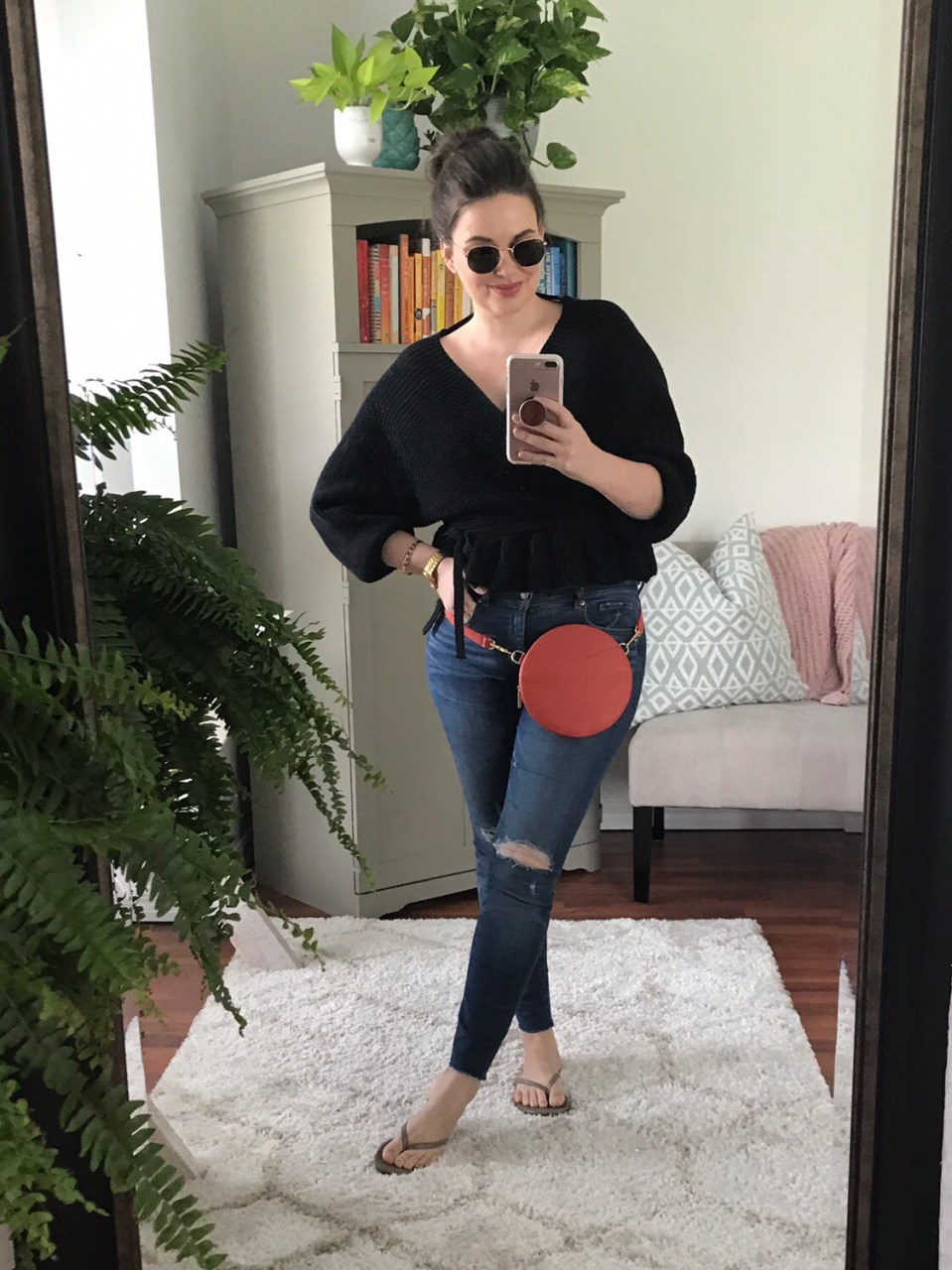 Style blogger wearing black cropped sweater with distressed skinny jeans and Cuyana mini circle bag in blood orange leather.