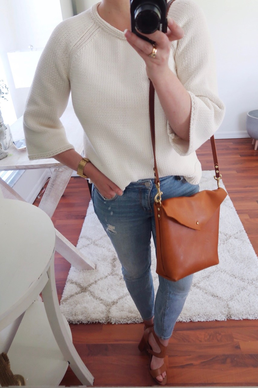 Style blogger wearing cream sweater and straight-leg jeans with a Neva Opet leather satchel handbag and cognac leather stacked heel sandals.