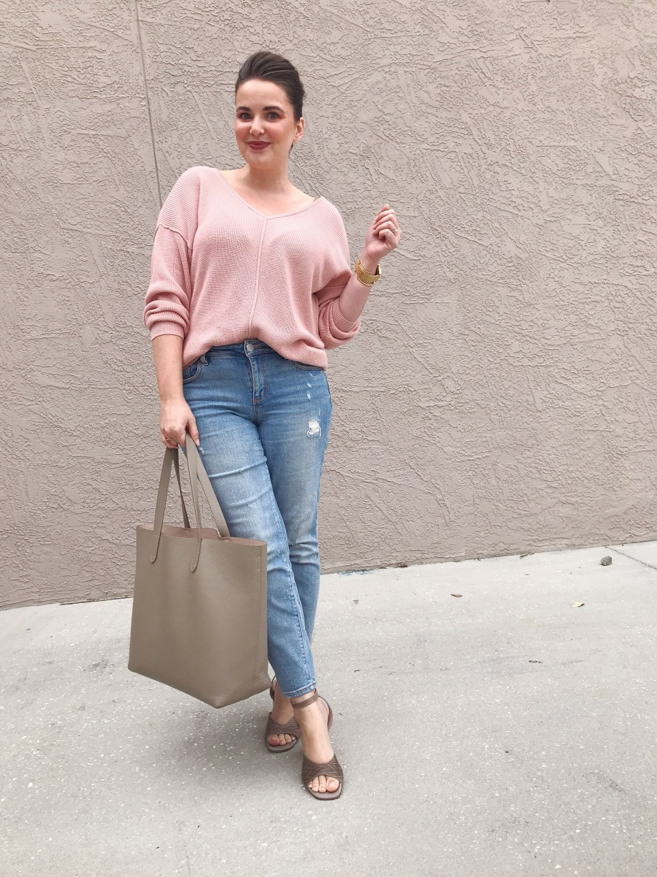 Style blogger wearing a pink sweater with distressed jeans, carrying a Cuyana structured leather tote